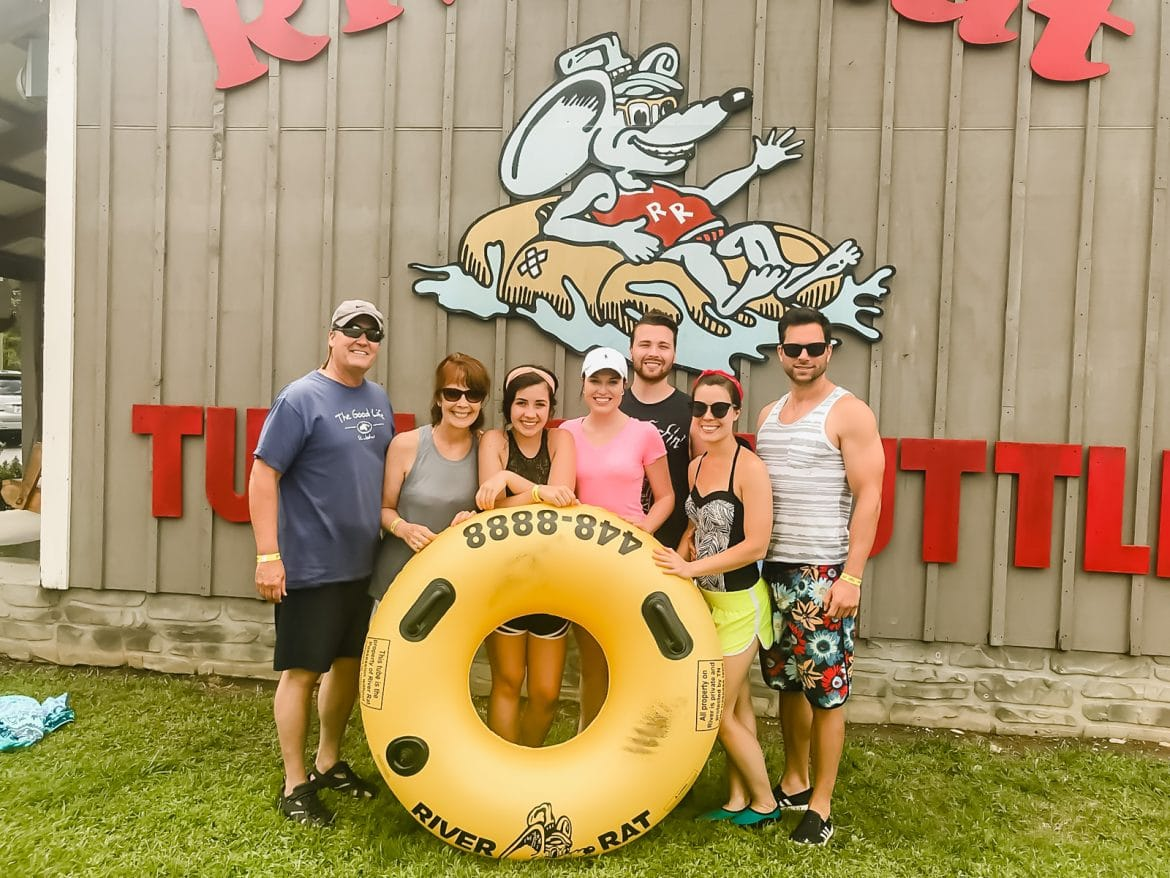 A family with a yellow inflated tube in front of the Smoky Mountain River Rat sign.