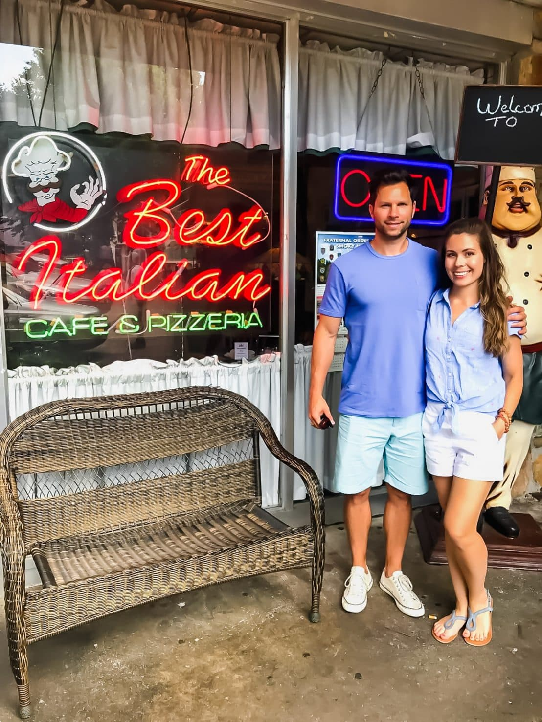 "A man and woman standing in front of a restaurant with a sign that reads ""The Best Italian Cafe and Pizzeria"""