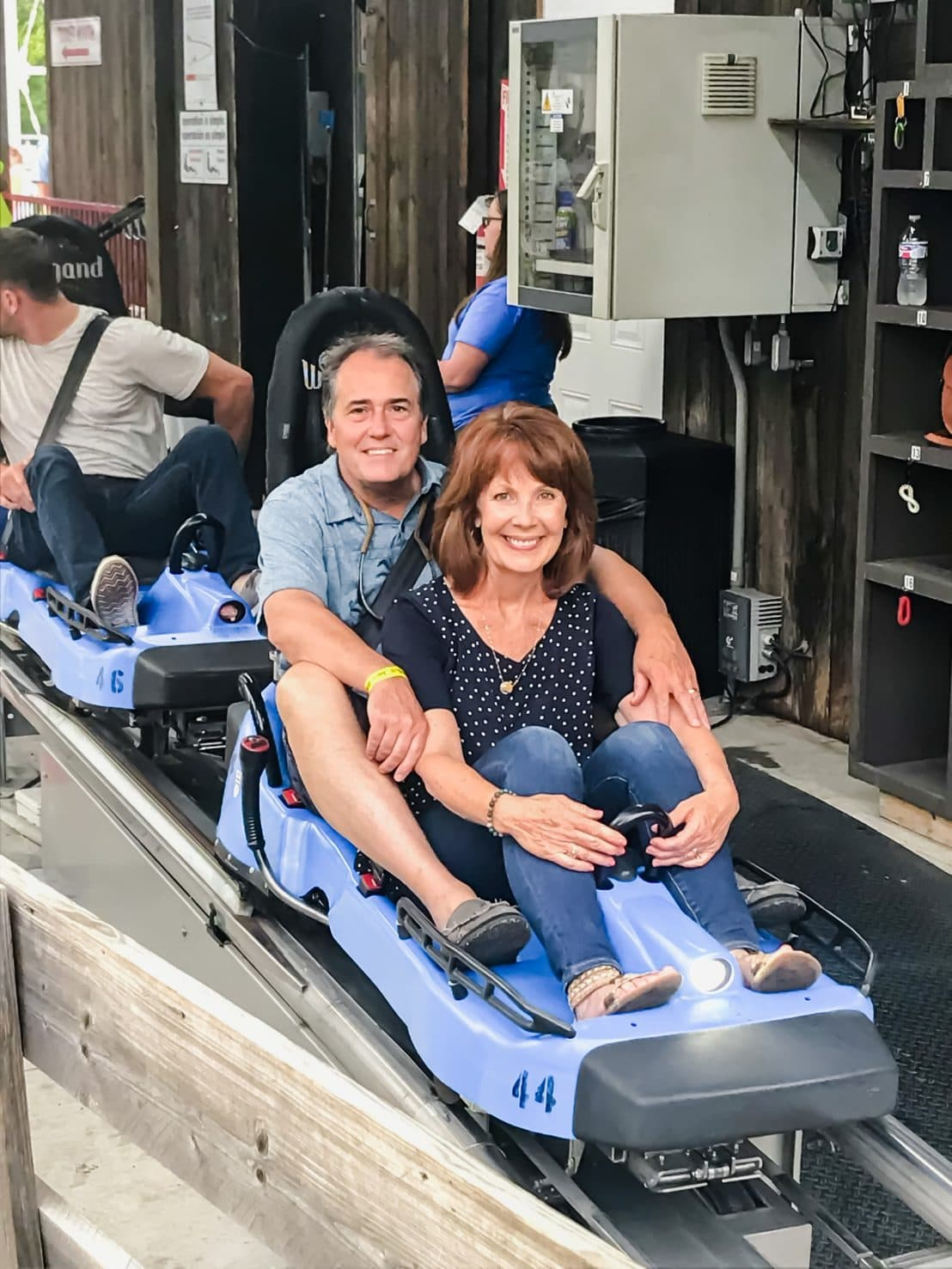 A man and woman in a blue kart on the Smoky Mountain Alpine Coaster.