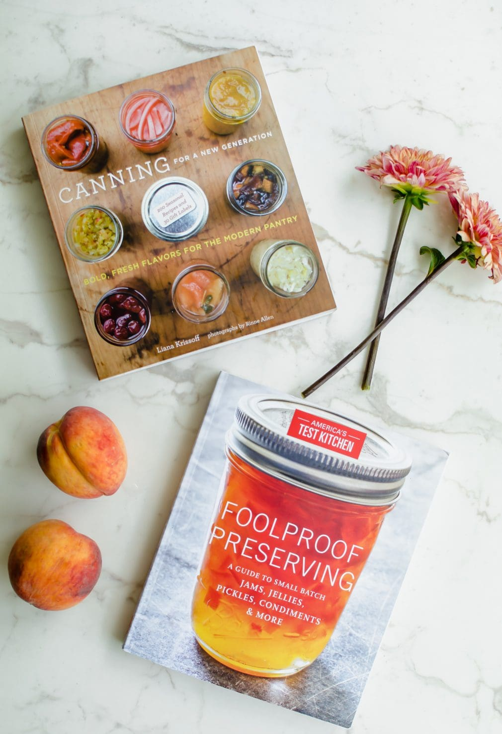 An overhead shot of two canning cookbooks with two dahlia flowers and fresh peaches on the side.