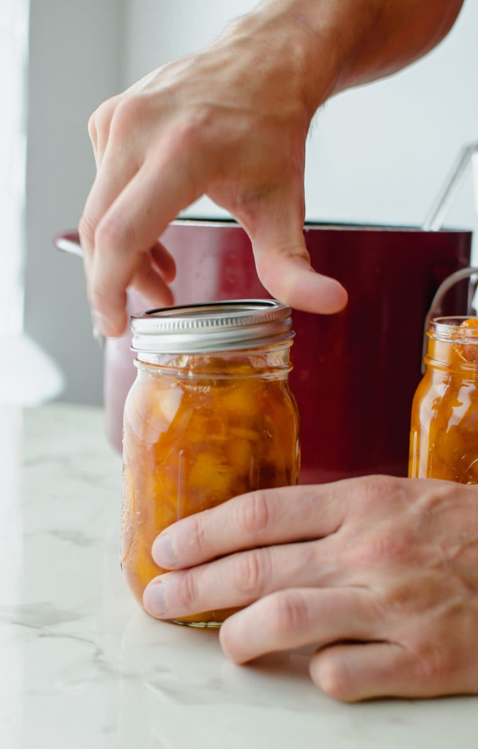 A pair of hands putting the lid on a canning jar filled with peach jam.
