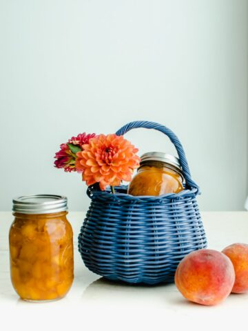 A shot of a blue wicker basket filled with dahlias and a jar of homemade peach jam.