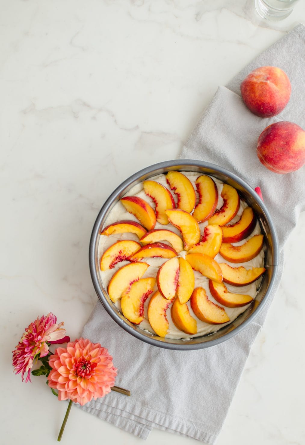 An overhead shot of an unbaked cake with yellow cake batter topped with fresh peaches on a white counter top.