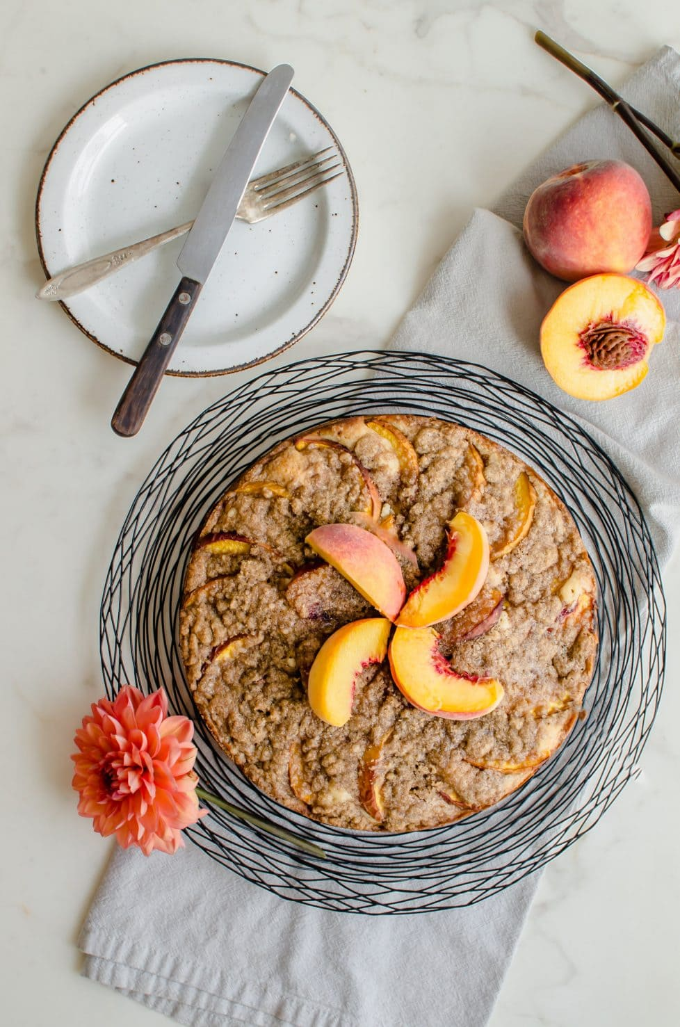 An overhead shot of a peach crumb coffee cake with sliced peaches on top, dahlias and fresh peaches on the side.