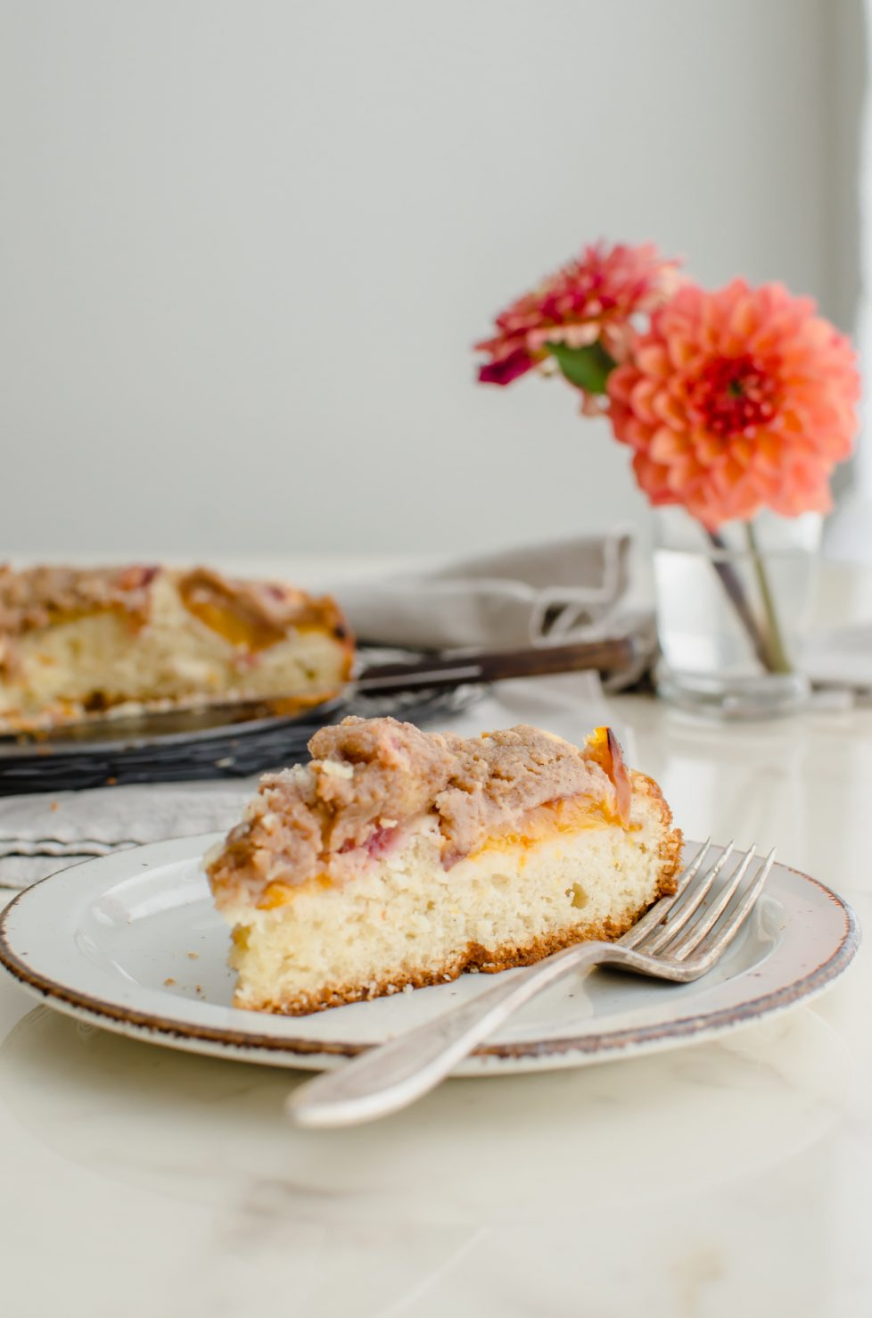 A slice of peach crumb coffee cake on a white countertop with a vase of dahlias in the background.