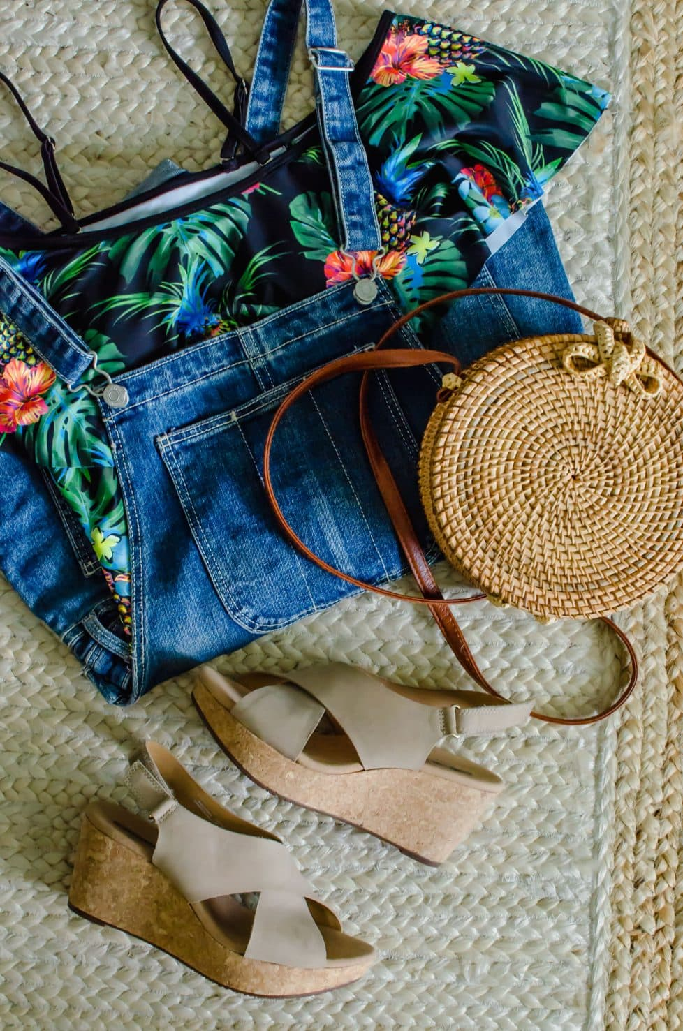 A flat lay of a summer outfit with a swimsuit, overalls, wedges, and a basket bag.