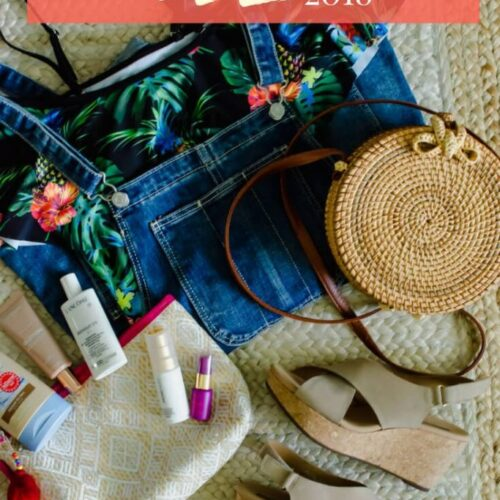 A flat lay photo of a swimsuit, overalls, sandal wedges, a wicker purse, and beauty products.