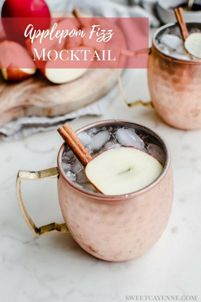 A moscow mule mug with a sparkling apple cider mocktail inside and a garnish of apple sliced and cinnamon stick.