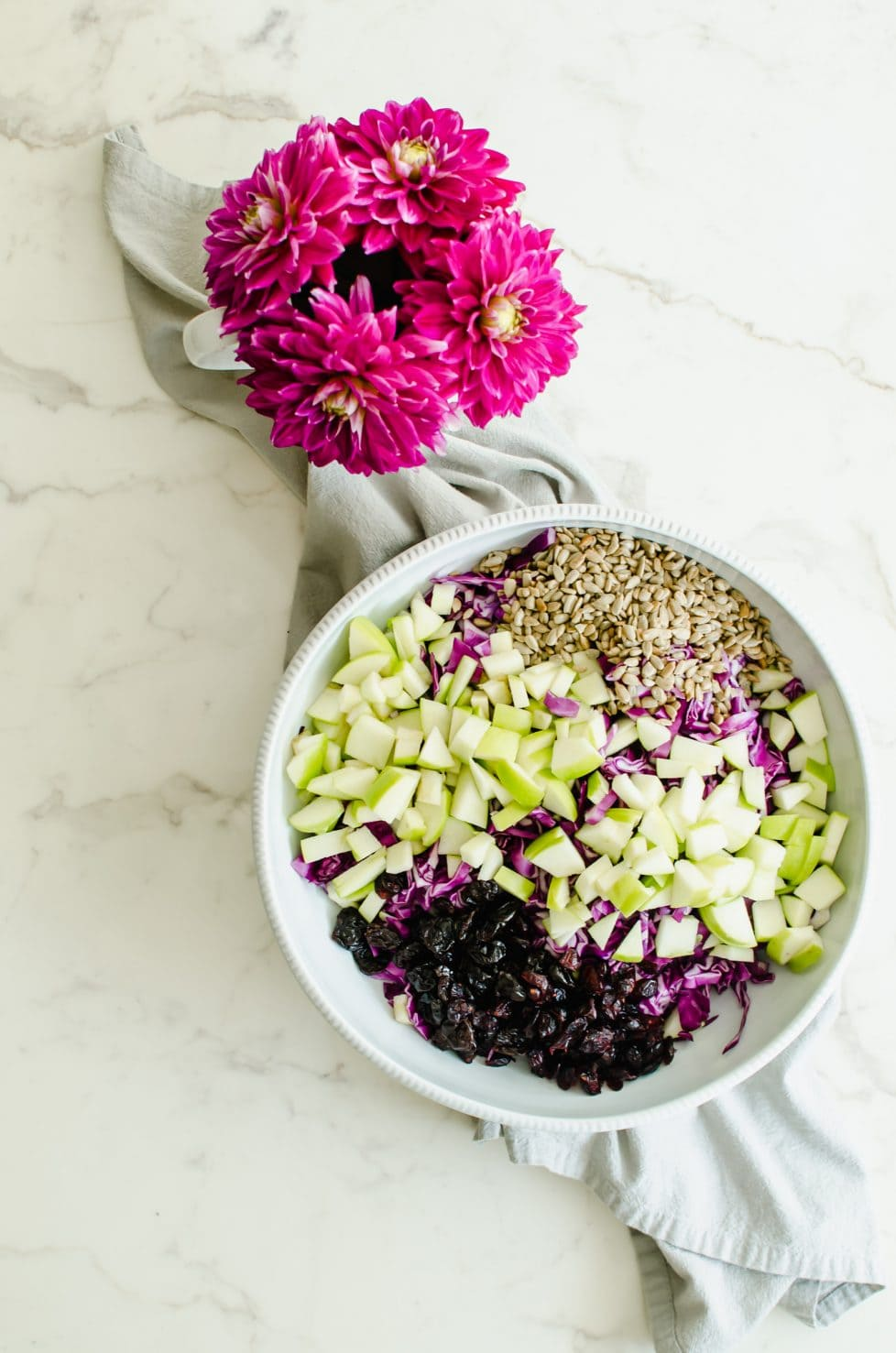 An overhead shot of shredded red cabbage, chopped green apple, sunflower seeds, and dried cherries in a large white bowl.