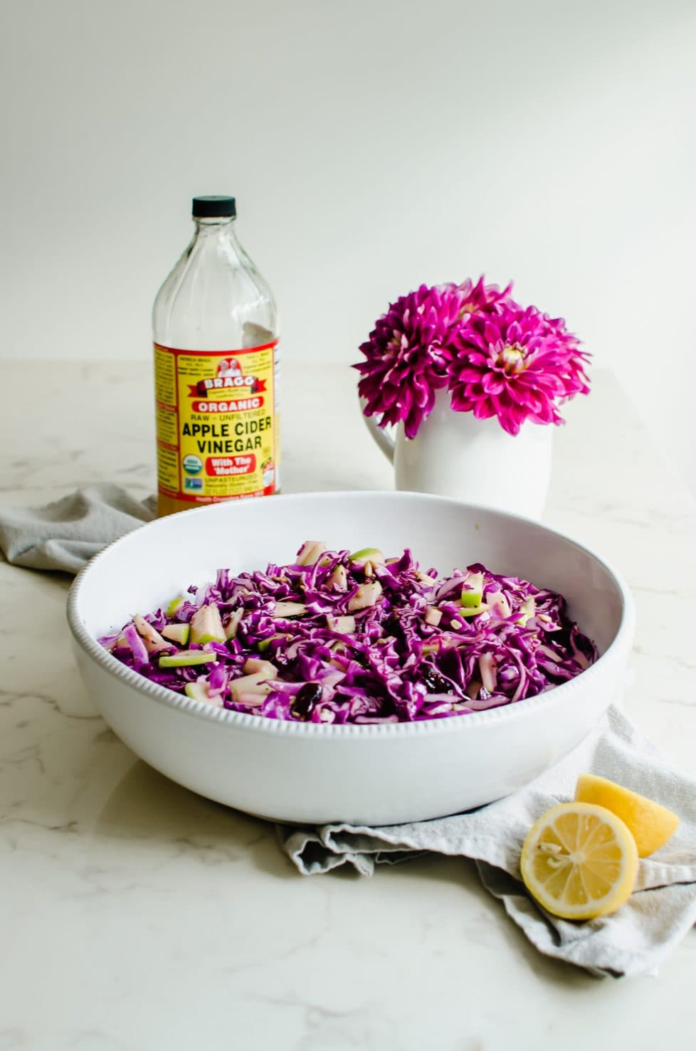 A large white bowl with red cabbage apple slaw, a bottle of cider vinegar, and a bouquet of pink dahlias.