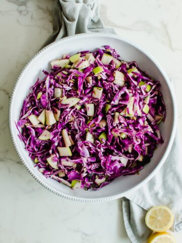 An overhead shot of a white bowl filled with red cabbage apple slaw.