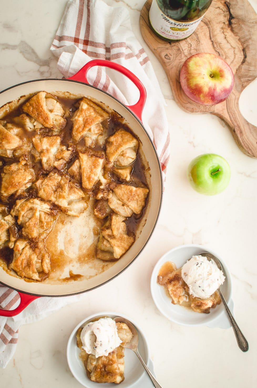 An overhead shot of apple dumplings in a red cast iron braised on a white counter top.