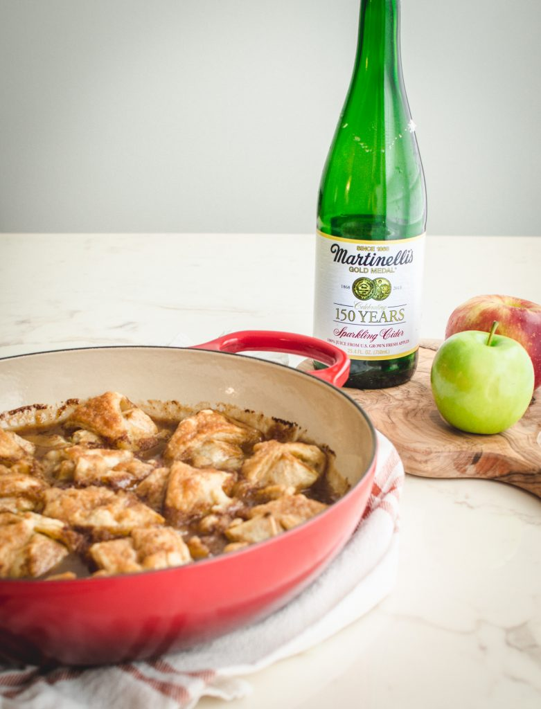A red cast iron braised with apple dumplings with a bottle of sparkling cider in the background.