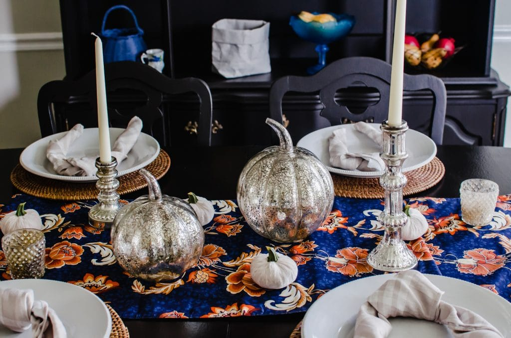 A fall table decor setting with mercury glass pumpkins, candlesticks, and a navy and orange table runner.