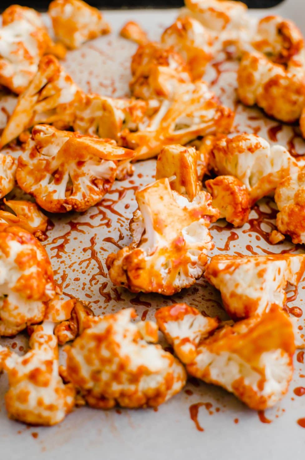 A close-up shot of cauliflower florets on a baking sheet coated in Korean-style sauce.