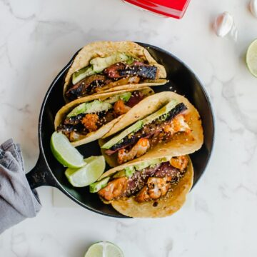 An overhead shot of a cast iron skillet filled with Korean-style beef tacos with roasted cauliflower.