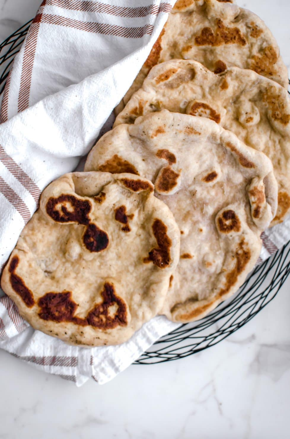 An overhead shot of a plate with pieces of naan and a plaid towel.