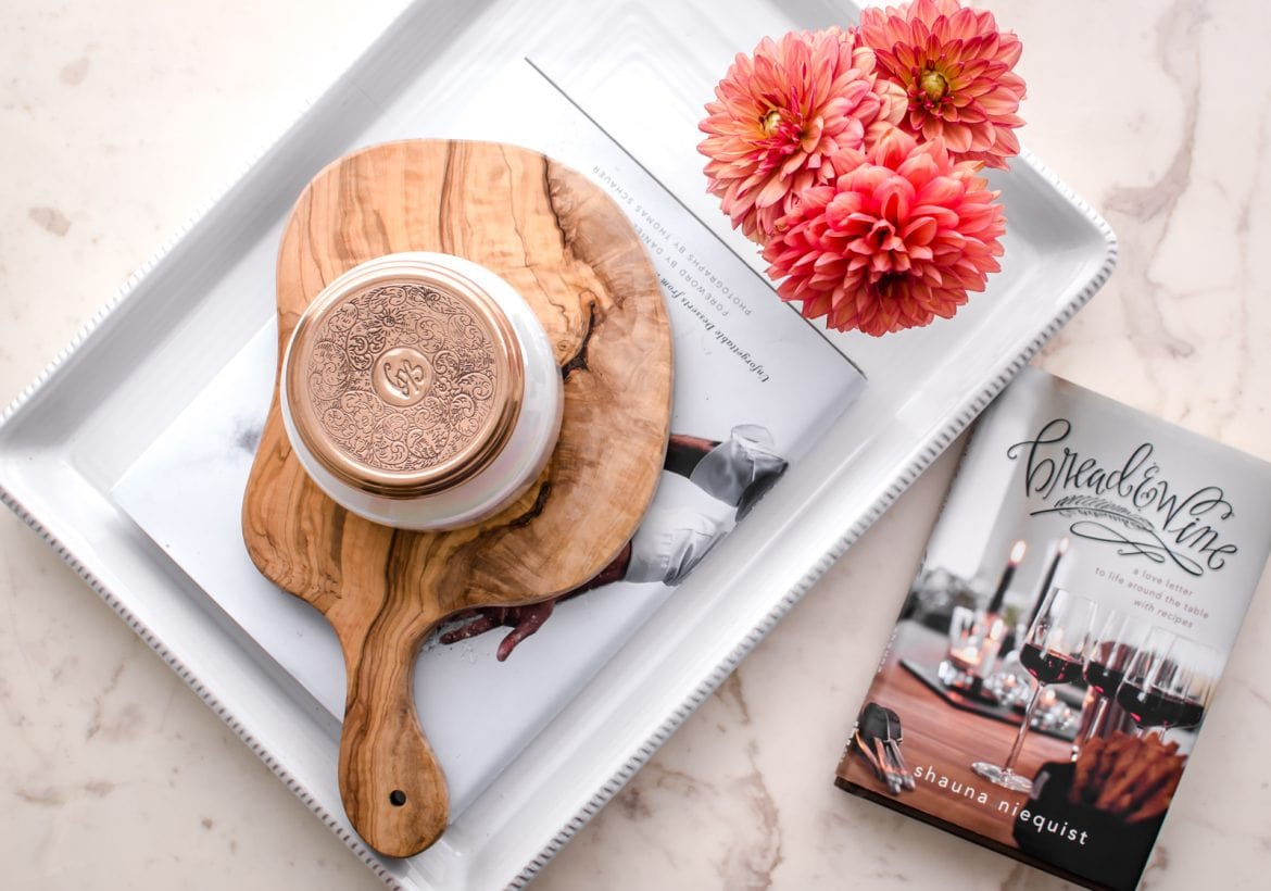 An overhead shot of the Bread and Wine book on a white counter with a tray of flowers on the side.