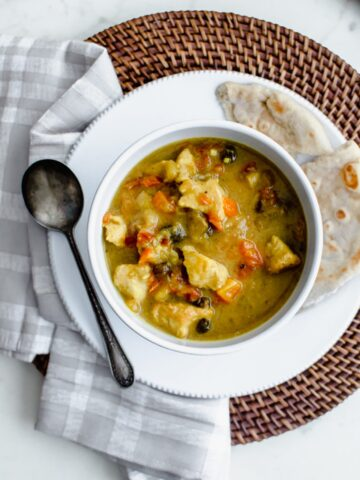 An overhead shot of a white bowl filled with Mango Chicken Curry on a rattan charger.