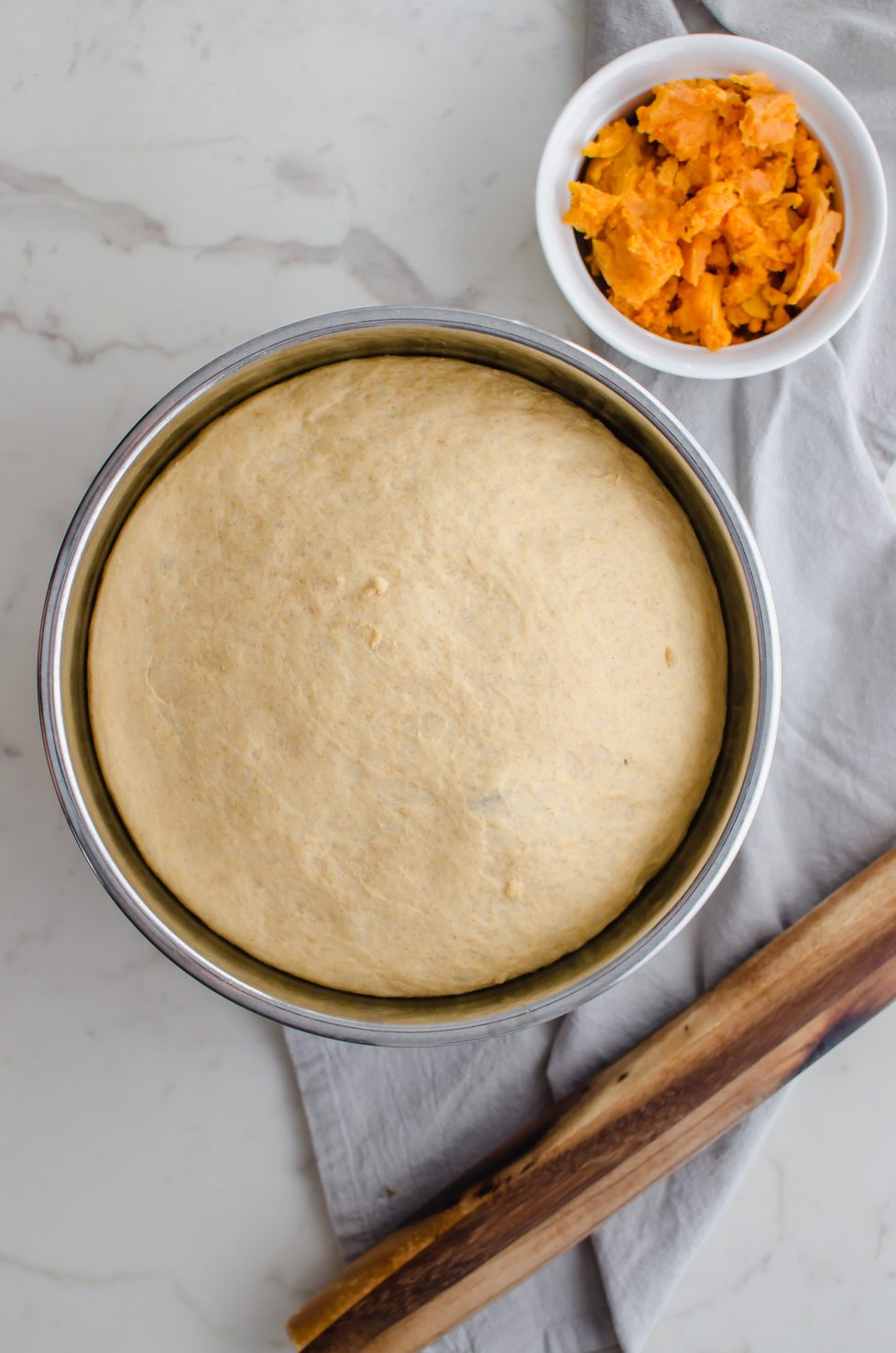 A bowl of risen sweet potato cinnamon roll dough with a rolling pin and grey towel on the side.