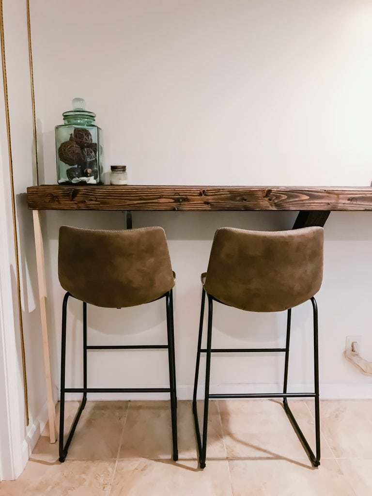 A photo of two leather chairs in front of a rustic wood counter top.