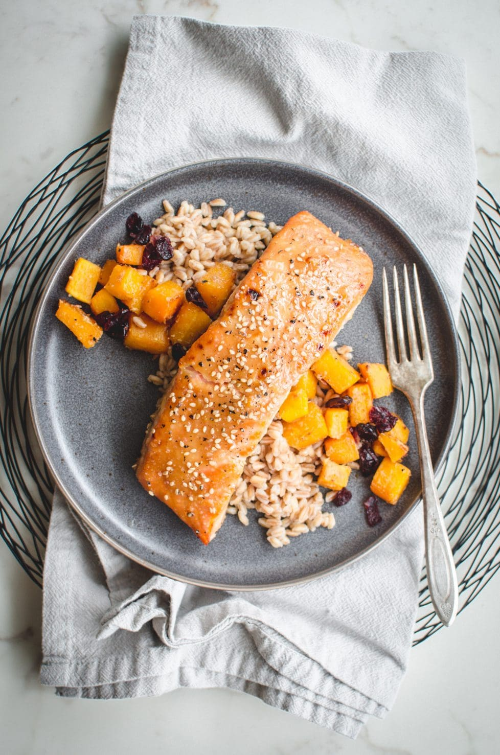 An overhead shot of a gray plate with miso maple roasted salmon, farro, and butternut squash on top.