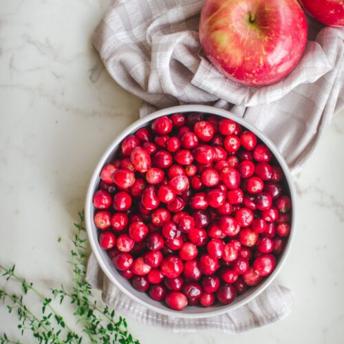 An overhead shot of a gray bowl with fresh cranberries, two apples and sprigs of thyme on the side.