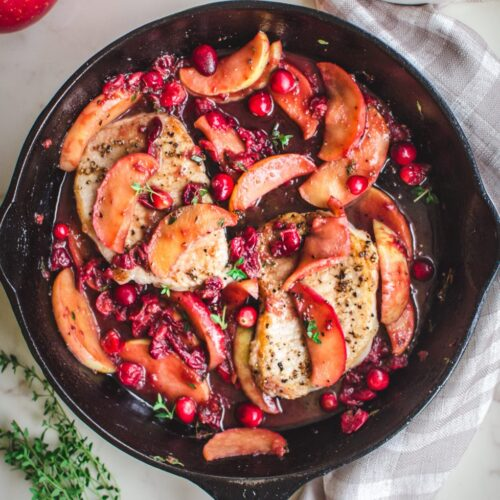 An overhead shot of pork chops in a skillet with a cranberry apple sauce.
