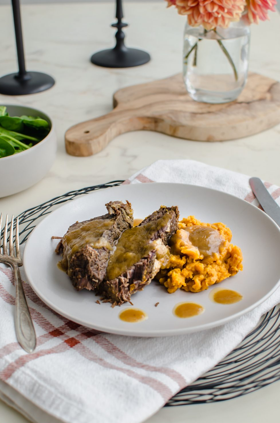 Beef roast on a plate with sweet potatoes and gravy.