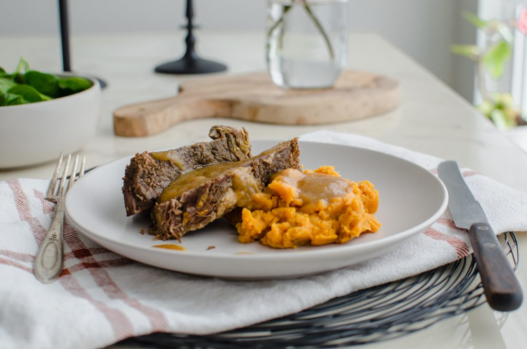 A side shot of a stone plate with beef pot roast, sweet potatoes, and cider gravy on top against a white marble background.