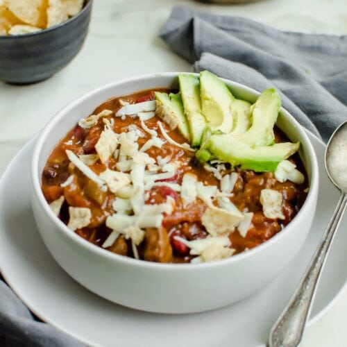 An overhead shot of a stone bowl with steak chili and topped with cheese and avocado.