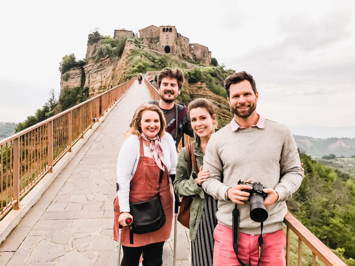 Two couples on the bridge in front of the Civita di Bagnoregio in Italy.