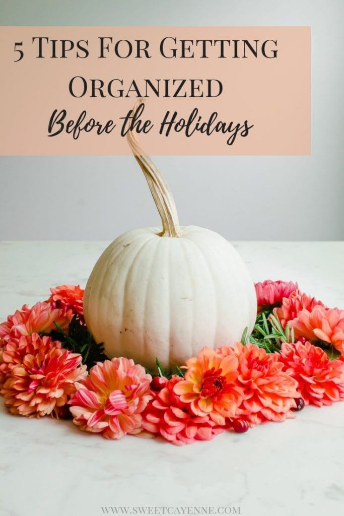 A white pumpkin surrounded by a wreath of coral-colored dahlia flowers.
