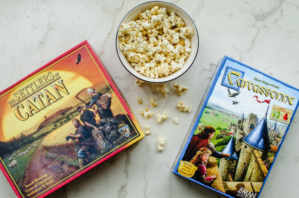 The CATAN and Carcassone board games on a white counter top and a bowl of popcorn.