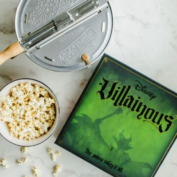 The Disney Villainous game next to a Whirly Pop and bowl of popcorn.