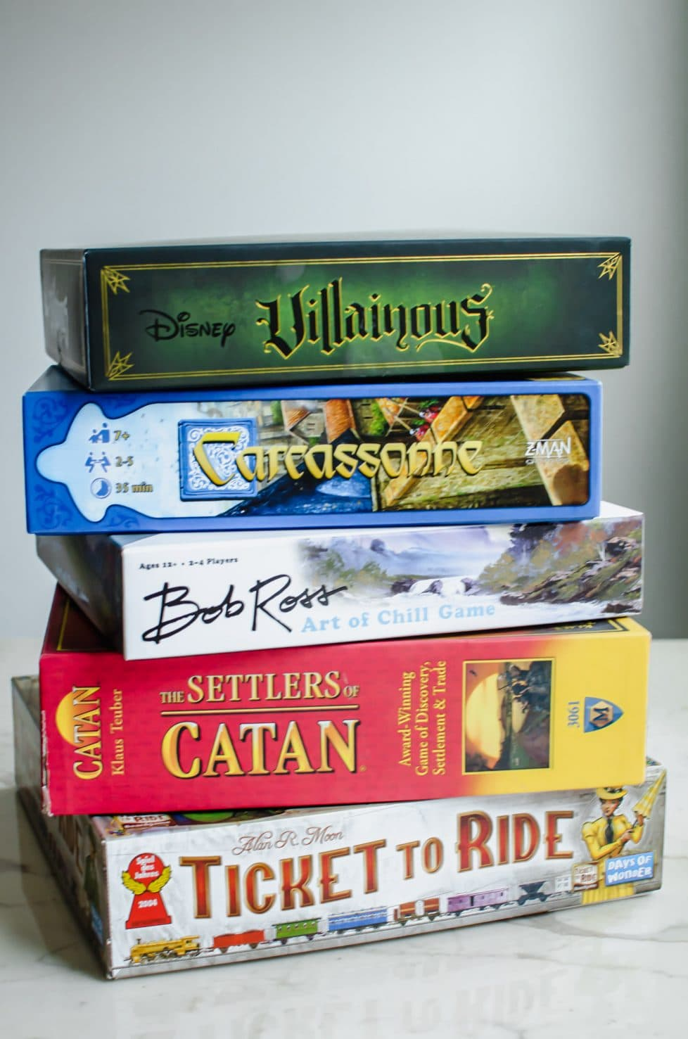 A stack of board games against a white background.