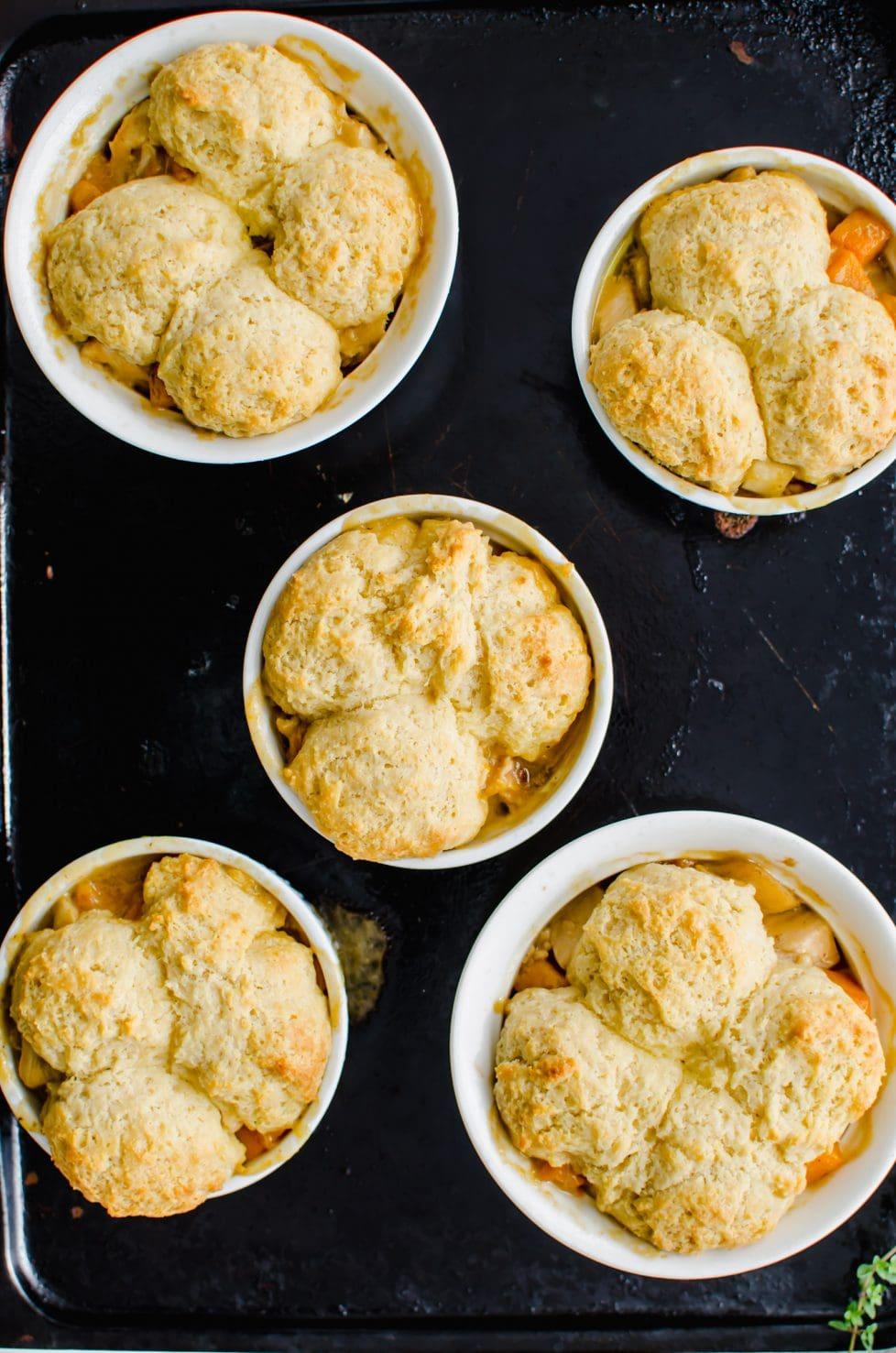 An overhead shot of a dark baking sheet with ramekins of turkey pot pie on top.