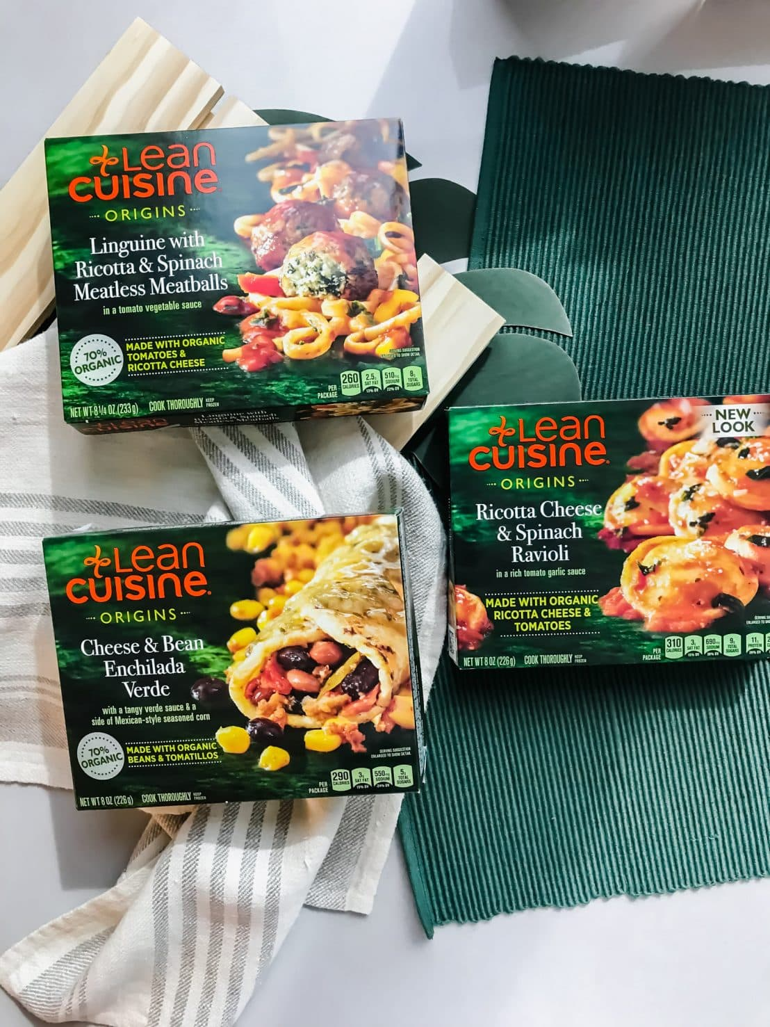 An overhead shot of three boxes of Lean Cuisine sitting on a green place mat.