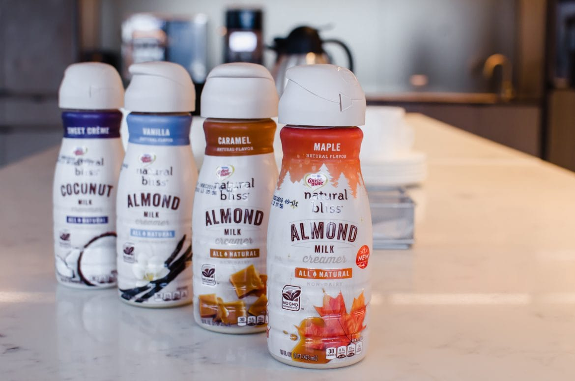 A line of Coffee Mate natural bliss creamers on a white counter top.