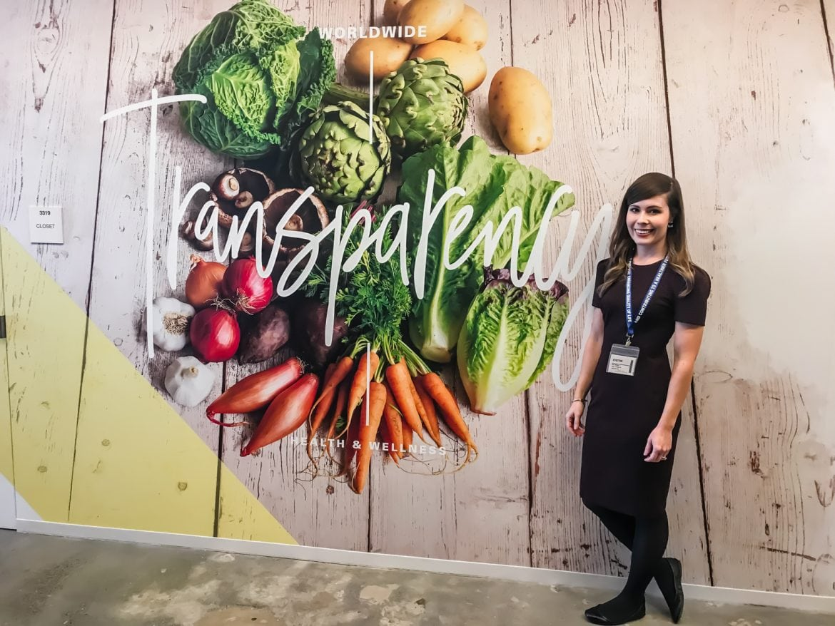 A young woman standing in front of a wall with a picture of produce and the word Transparency.