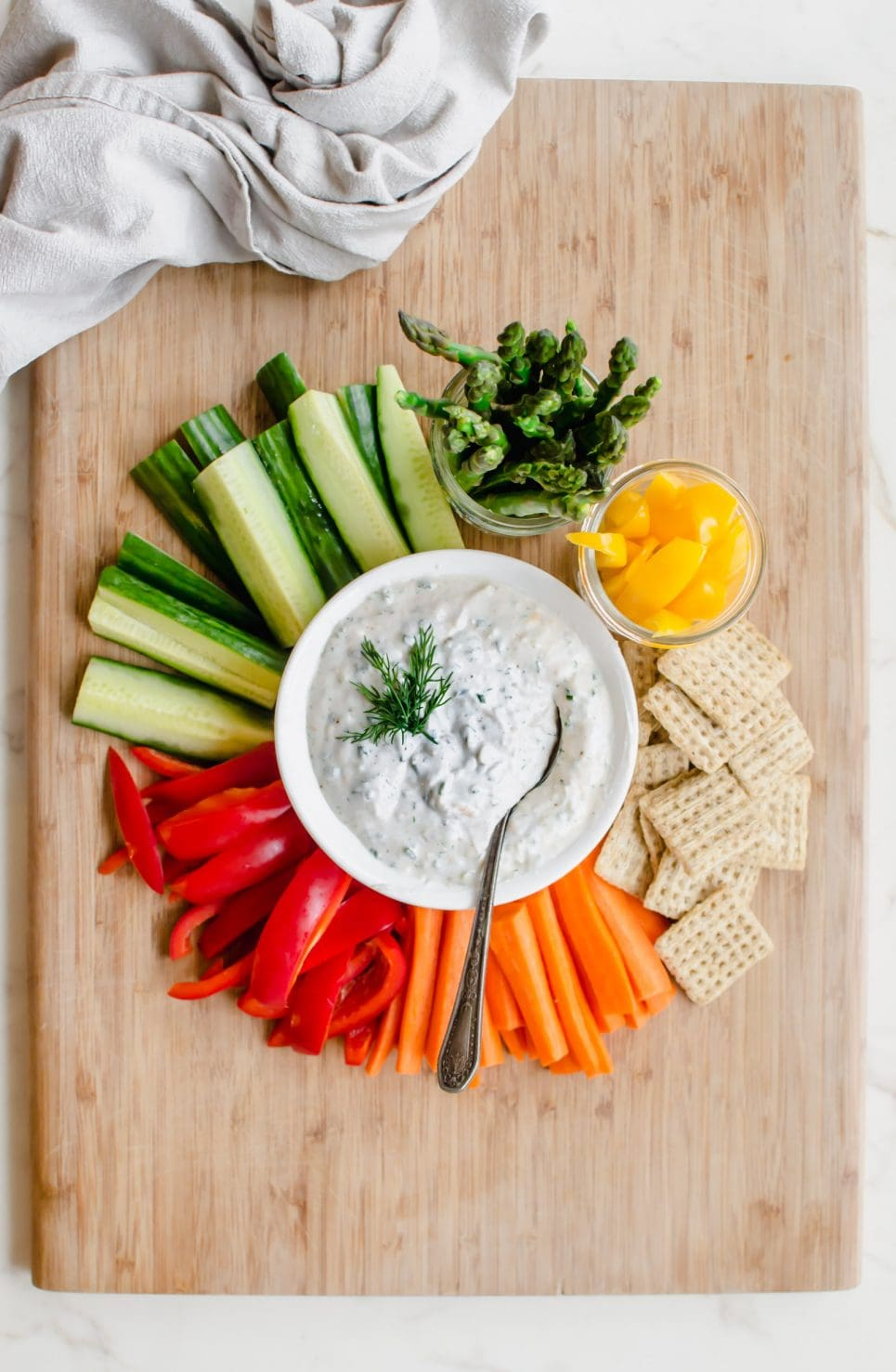 A cutting board with colorful veggies surrounding a white bowl with creamy Parmesan herb dip.