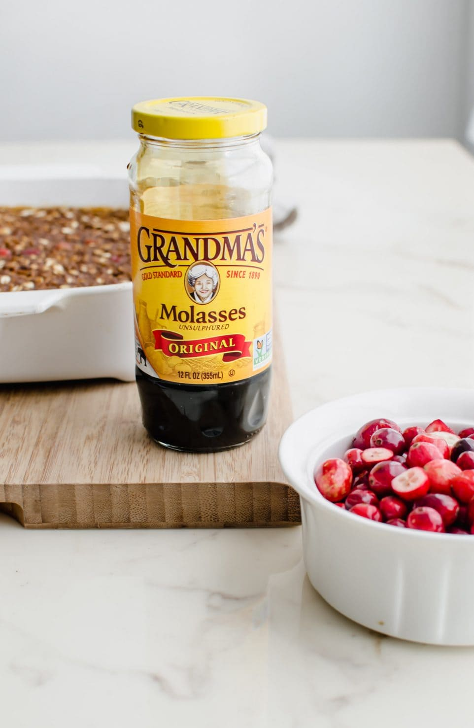 A bottle of Grandma's molasses next to a bowl of cranberries and gingerbread baked oatmeal.
