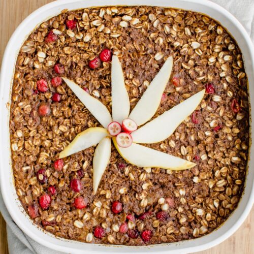 A white casserole dish filled with gingerbread baked oatmeal and topped with pear slices.
