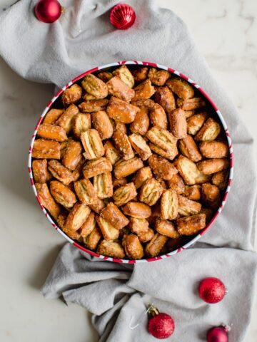 A Christmas treat tin filled with Ranch pretzel mix sitting on a grey dish towel.