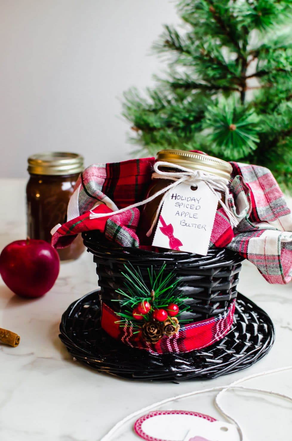 A basket shaped like a black hat with a plaid dish towel and jar of apple butter inside.