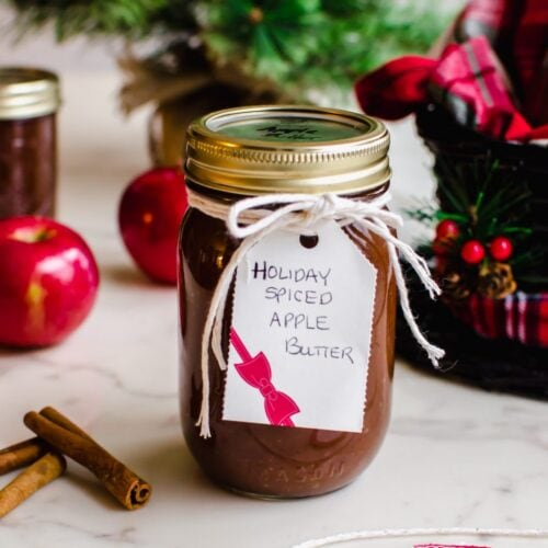 A jar of apple butter wrapped with twine and a gift tag with other jars and a Christmas tree in the background.