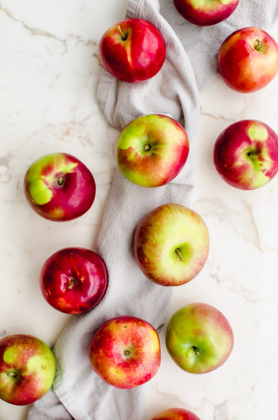 An overhead shot of a bunch of apples sitting on a light grey dish towel.