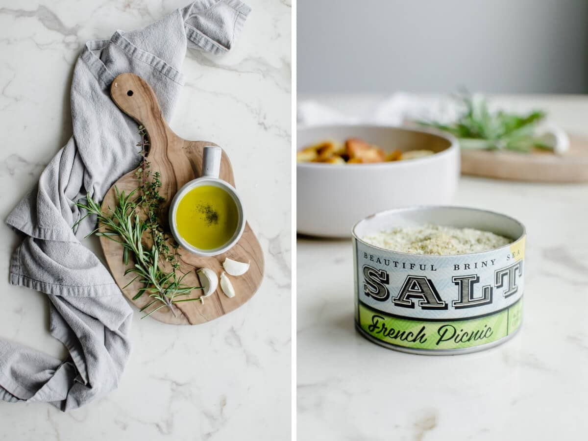 A cutting board with herbs, a bowl of olive oil, and a container of sea salt.