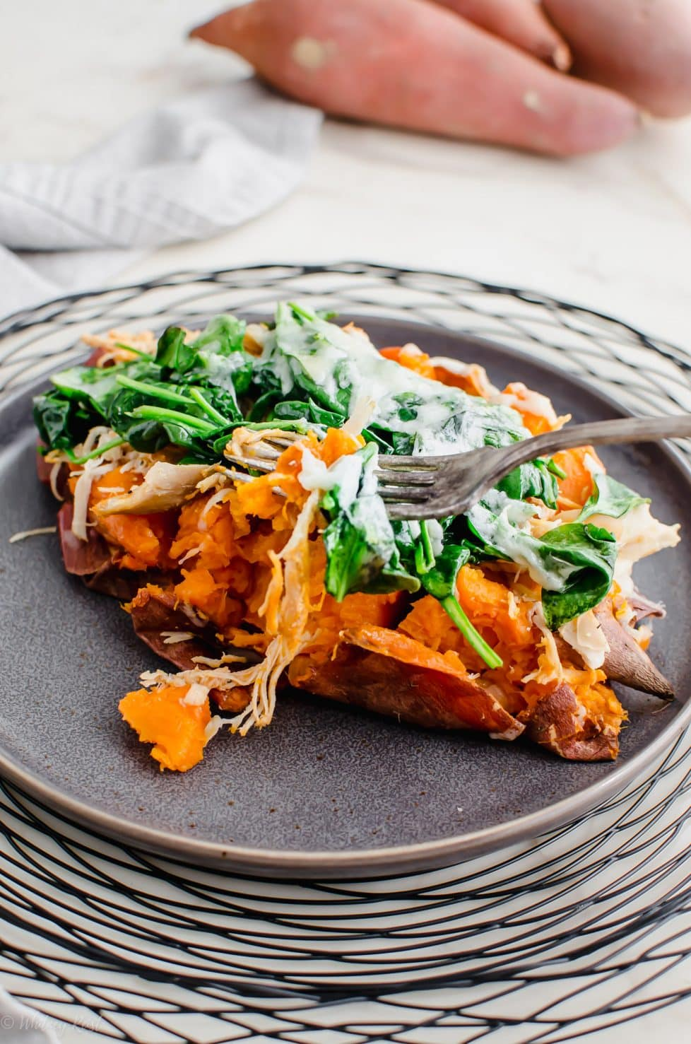 A grey plate with a Buffalo Chicken Stuffed Sweet Potato on top.