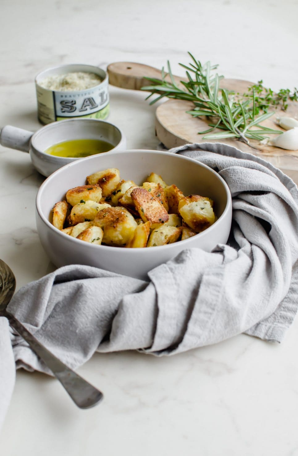 A grey bowl filled with crispy roasted potatoes with bowls of salt and olive oil on the side.